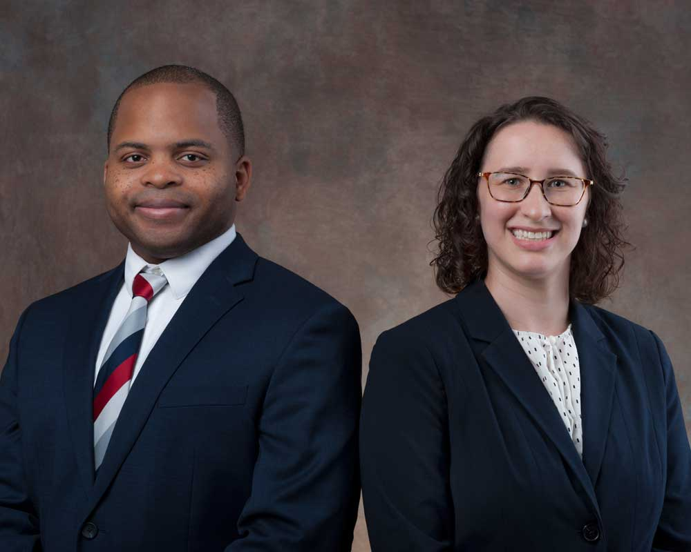 portrait of man and woman standing beside each other wearing suits